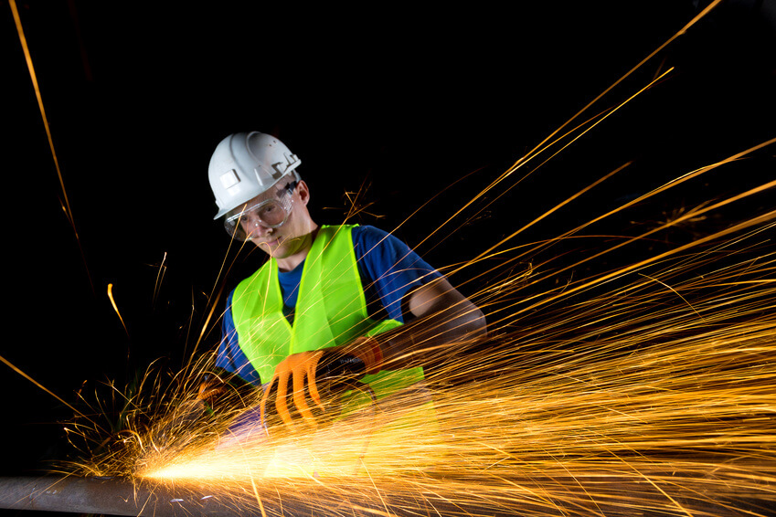 worker with angle grinder wearing safety goggles