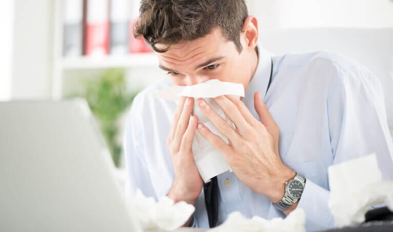 Man Sneezing At Desk